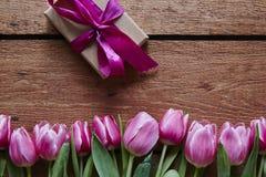 Un par de tulipanes rosados y un regalo envuelto para el día de tarjetas del día de San Valentín Fotografía de archivo libre de regalías