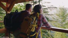 Un par de turistas admiran la hermosa vista del bosque de la plataforma de observación En la puesta del sol almacen de video