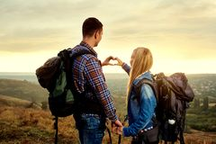 Un par de turistas con las mochilas hicieron un símbolo del corazón w Fotografía de archivo