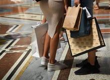 Un par de turistas con los panieres en la galería Vittorio Eman foto de archivo libre de regalías