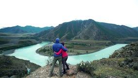 Un par de turistas se están colocando encima de una montaña de piedra y abrazando, un río rápido de la montaña fluye abajo Visión almacen de video