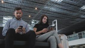 Un par de turistas utilizan sus artilugios mientras que esperan la cola para el enregistramiento en el aeropuerto, tecnología, vi almacen de video