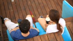 Un par de un individuo y una muchacha están bebiendo el café y están charlando en un café al aire libre informal Alimentos de pre almacen de video