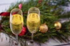 Un par de vidrios con champán del oro en una tabla de madera blanca Imagen de archivo