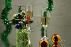 Un par de vidrios con champán en una tabla de madera con las bolas de la Navidad, una cinta roja con una puntilla de la picea en  Imagenes de archivo