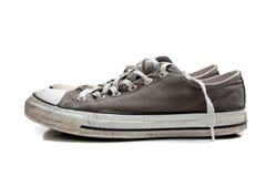 Un par de zapatillas de deporte grises en blanco Fotografía de archivo libre de regalías
