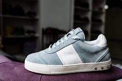 Un par de zapatillas de deporte azules del ante en un lenguado blanco con los acentos blancos en un fondo de la tienda imagen de archivo libre de regalías