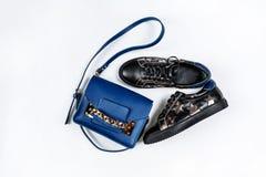 Un par de zapatillas de deporte de cuero negras con las estrellas de plata y de un bolso azul con una cadena del oro en un fondo  imágenes de archivo libres de regalías