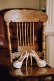 Un par de zapatos blancos hermosos de la boda con los tacones altos se coloca en una silla de madera del vintage Imagen de archivo