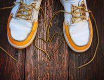 Un par de zapatos de la cubierta en un pórtico de madera agradable con los cordones en un corazón forma Fotografía de archivo libre de regalías