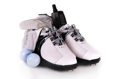 Un par de zapatos del golf, dos pelotas de golf, un guante de golf Imagen de archivo libre de regalías