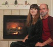 Un par delante de una chimenea en la Navidad Imagen de archivo libre de regalías