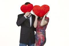 Un par en amor con dos corazones rojos en el día de tarjeta del día de San Valentín Foto de archivo libre de regalías