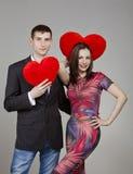 Un par en amor con dos corazones rojos en el día de tarjeta del día de San Valentín Foto de archivo