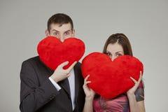 Un par en amor con dos corazones rojos en el día de tarjeta del día de San Valentín Fotografía de archivo libre de regalías