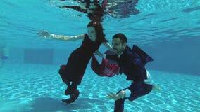 Un par en amor, la novia y novio, nadada debajo del agua en la piscina en vestidos de boda Sonríen, gozan y juegan metrajes