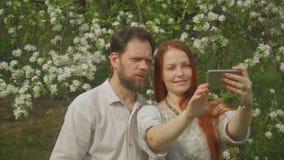 Un par en amor mira las fotos en la pantalla del smartphone y toma un selfie almacen de video