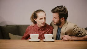 Un par en el amor que come café, sentándose en un sofá, hablando el uno al otro y sonriendo feliz almacen de metraje de vídeo