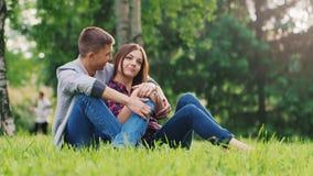 Un par en el amor que descansa en el parque, sentándose en un abrazo en el césped, hablando almacen de metraje de vídeo