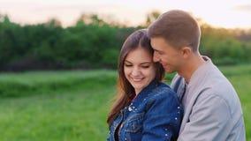 Un par en el amor que descansa en el parque, sentándose en un abrazo en el césped, hablando metrajes