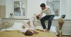 Un par en el dormitorio que hace algunas imágenes, individuo joven que toma la foto para las memorias de su novia en cama acogedo metrajes
