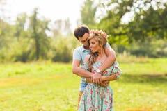 Un par en los hombres jovenes hermosos del amor que abrazan en un verano parquea en un día soleado Imagen de archivo