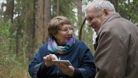 Un par envejeció, mirando las fotos de nietos en un smartphone Sonriendo y riendo, experimentando alegría Amor almacen de metraje de vídeo