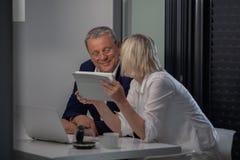 Un par envejecido medio en la tabla con sus dispositivos imagen de archivo libre de regalías