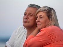 Un par envejecido medio que se sienta cerca de uno a y que mira en la distancia, sonriendo fotografía de archivo libre de regalías
