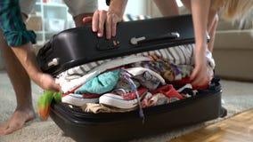 Un par está intentando cerrar la maleta hasta los topes almacen de metraje de vídeo