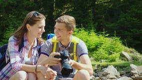 Un par feliz de turistas mira a través de las fotos capturadas en la cámara Grandes vacaciones y buenas memorias almacen de metraje de vídeo