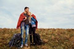 Un par feliz de turistas se está calentando debajo de una tela escocesa fotografía de archivo