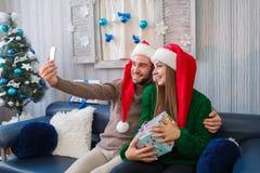 Un par feliz en sombreros del ` s de Papá Noel está haciendo el selfie en el teléfono móvil, sosteniendo una caja de regalo dentr foto de archivo