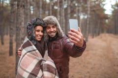 Un par feliz que hace el selfie en el bosque del otoño al aire libre fotos de archivo