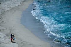 Un par, hombre y mujer, tomando imágenes en la playa imagen de archivo libre de regalías