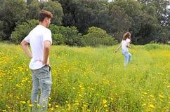 Un par joven adolescente que se divierte en un campo del crisantemo Imagen de archivo libre de regalías