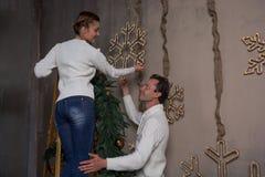 Un par joven adorna una casa para la Navidad con las guirnaldas de Imagen de archivo