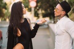 Un par joven, atractivo de amantes presenta para una cámara en las calles foto de archivo libre de regalías