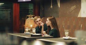 Un par joven atractivo está descansando en un café almacen de video