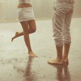 Un par joven cariñoso que abraza y que se besa debajo de una lluvia Amantes m Fotos de archivo