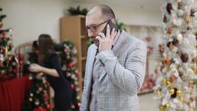 Un par joven compra decoraciones de la Navidad en la tienda El marido que habla en el teléfono, y la esposa elige la Navidad almacen de metraje de vídeo