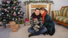 Un par joven joven da presentes a la cámara para el espectador Tema de la Navidad y del Año Nuevo Imágenes de archivo libres de regalías