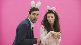 Un par joven de los amantes aparece en el fondo rosado, reproduciendo caballos de liebres Con los oídos de un conejo rosado en