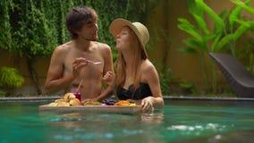 Un par joven de los turistas de la luna de miel desayuna su propio personal en una tabla flotante en una piscina privada metrajes