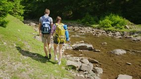 Un par joven de los turistas que caminan a lo largo de un río de la montaña contra un fondo del viaje verde y del active del bosq almacen de metraje de vídeo