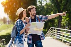 Un par joven de los turistas que se colocan en el parque y que sostienen un mapa Piensan adonde ir después Fotografía de archivo
