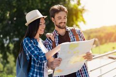 Un par joven de los turistas que se colocan en el parque y que sostienen un mapa Piensan adonde ir después Imagen de archivo