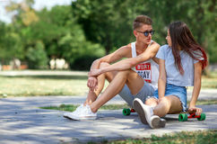 Un par joven dulce del caída-en-amor que se sienta en la tierra en un fondo borroso del parque Relación y concepto del amor Imagenes de archivo