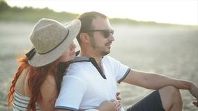 Un par joven en amor es de reclinaci?n y que disfruta de la salida del sol en la playa Tienen mucha fecha del gasto de la diversi metrajes