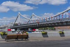 Un par joven en un banco delante del puente crimeo en Moscú Mundial 2018 de la FIFA foto de archivo